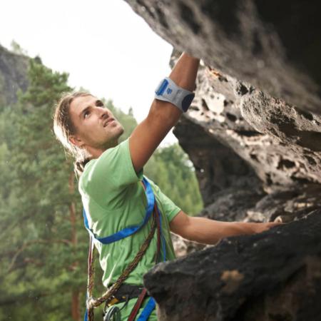 Junger Mann beim Klettern mitEllenbogenspange Bauerfeind EpiPoint